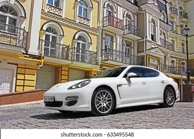 White Porsche. Porsche Panamera on the background of beautiful buildings.  Kyiv, Ukraine, June 25, 2015; Editorial photo.