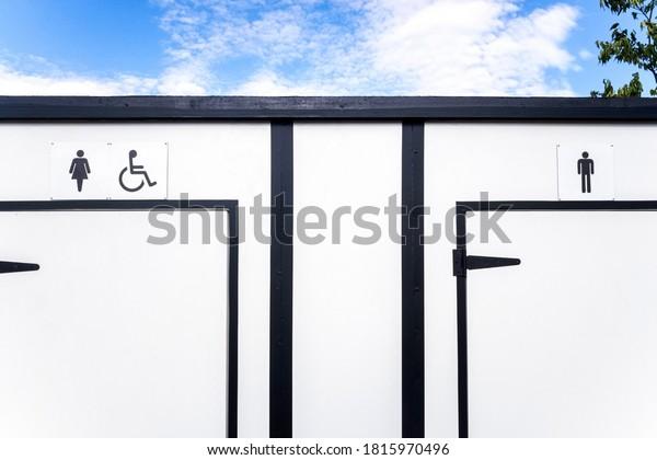 Retretes blancos portátiles con espacio para mujeres, hombres y discapacitados.