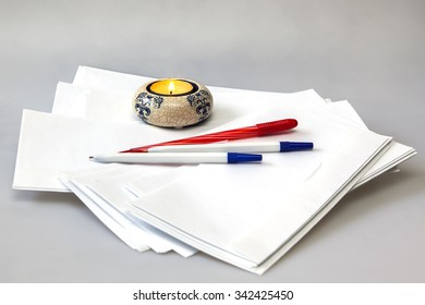 White post envelopes and the burning candle in a candlestick
