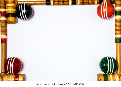 white poster board framed with wooden croquet mallets and balls with room for copy in middle