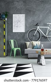 White poster on grey textured wall above mint chair in living room with triangle carpet and bike above sofa