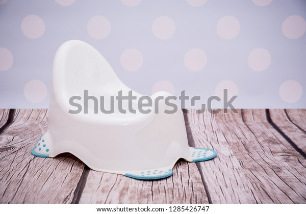 White potty on a light, pastel childish background. Concept of peeing a child into a potty. Learning to pee, the life of an infant, a small child. Children's development stage.