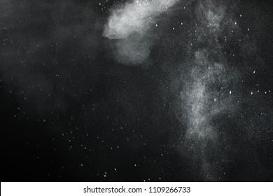 White Powder explosion on black background. White dust exploding.Paint Holi