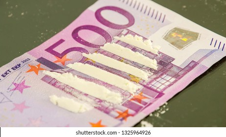 The white powder lined on the top of a 500 Euro bill. A bunch of white powder on top of the 500 Euro bill is cut into six pieces by a hard white paper.