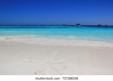 White powder sand and turquoise blue sea water under clear blue sky at Tachai island of Surin islands Marine National park, Thailand - Shutterstock ID 737288338