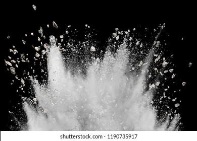 White powder with small stones explosion on black background. Small granite rock stone splash against dark background.