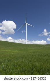White power generating wind turbines, windmills against  blue sky, white clouds, on green Spring wheat fields.