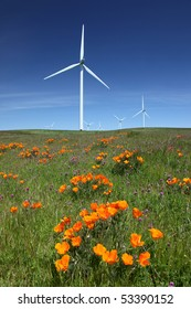 White power generating wind turbines, windmills against  blue sky, orange wildflowers, california poppies, on agricultural green pastures