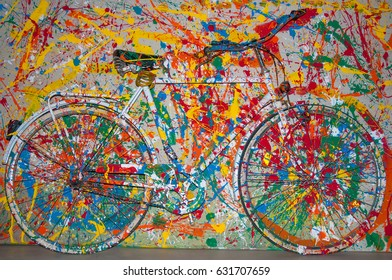 White power socket and switch on the wall with color bicycle as decoration. old painted bicycle attached to the wall in art office toned to bright color. vintage bicycle on decorative color wall