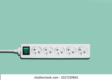White power strip, white power supply with green switch. White power supply on a green, pastel background. The concept of electricity savings, electricity increases, problems with the socket.