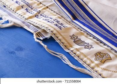 White Prayer Shawl - Tallit, jewish religious symbol. Part of the prayer is written in Hebrew on the shawl