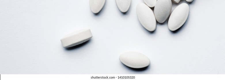 White Prescription Pills Tipped Out and Spilled from container bottle on white background, drug addiction concept, pharmaceuticals, medicine and medical concept