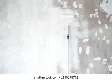 white primer painting with roller brush on the repair decoration cement wall construction background