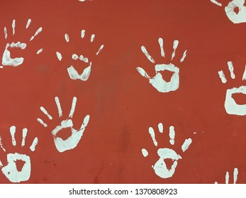 White print hands icon on the red wall.