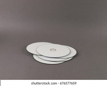 Lot of white printable discs a pile against gray background