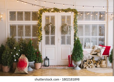 The white private house is decorated with small Christmas trees and lanterns, a bag of gifts. A bench with pillows near the front door of the house and wood under it