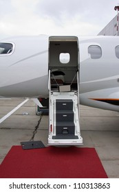 white private jet and open ladder, red carpet at the airport on a background cloudy sky