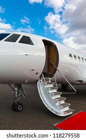 white private jet and open ladder, red carpet at airport on background blue sky