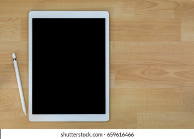 White pro tablet computer with blank black screen next to white ipad pencil pen on wooden background with copyspace