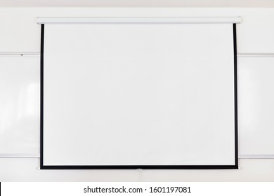 White projection screen over a white board on the classroom wall. Close up with copy space.