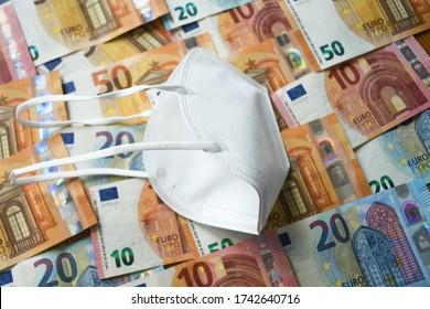 Masque de visage médical de protection blanc posé sur la monnaie de l'Union européenne Euro différents billets de papier