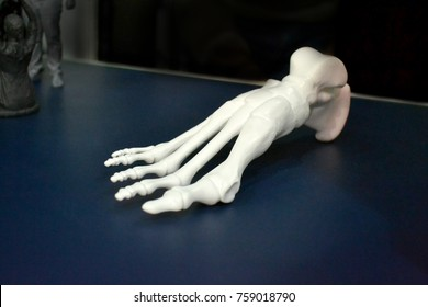 White prototype of the human foot skeleton printed on 3d printer on dark surface. Fused deposition modeling, FDM. Progressive modern additive technology. Concept of 4.0 industrial revolution