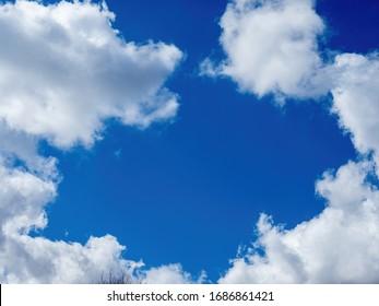 weiße Puffwolken und hellblauer Himmel