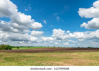 White, puffy clouds moving over remote dirt road and flat lands in the Great Plains, Oklahoma.