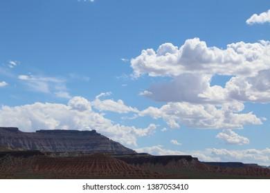 white puffy clouds over utah mesas