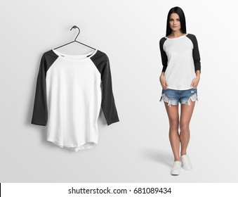White pullover, long sleeve baseball t-shirt on a young woman in shorts, isolated mockup. Hanging t-shirt long sleeves, against empty wall.