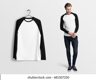 White pullover, long sleeve baseball t-shirt on a man in jeans, isolated mockup. Hanging t-shirt long sleeves, against empty wall.