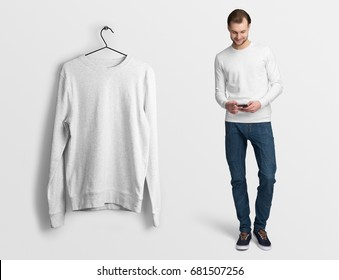 White pullover, long sleeve t-shirt on a man in jeans, holding a smartphone, isolated, mockup. Pullover, hoodie mockup on hanger, hanging against empty wall background.