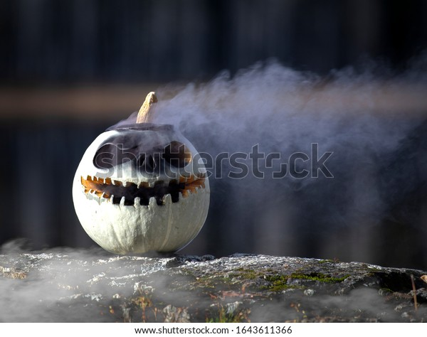 White pumpkin sitting on a rock with smoke coming out of the lid with water in the background.