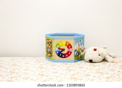 white puppy doll and watch toybox on bed with white background.