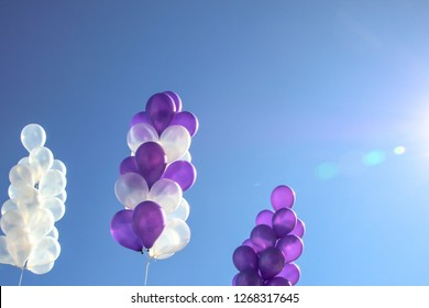 White and purple balloons on the sky background.