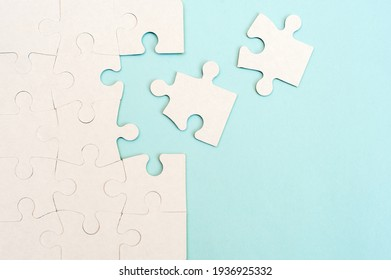 White puzzle background with missing piece on blue background. Top view