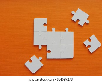 White puzzle jigsaw on orange background.