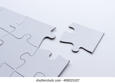 White puzzle on white background with missing piece.