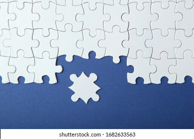 White puzzle on a colored background top view.