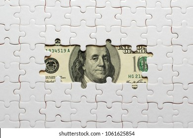 white puzzle on hundred dollars banknotes.
