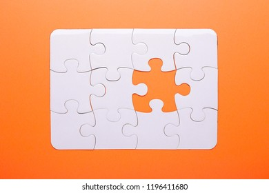 White puzzle on orange background. Missing piece. Top view