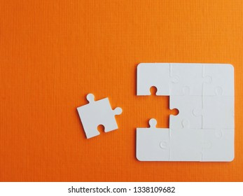 White puzzle pieces on orange background,Business success concept.