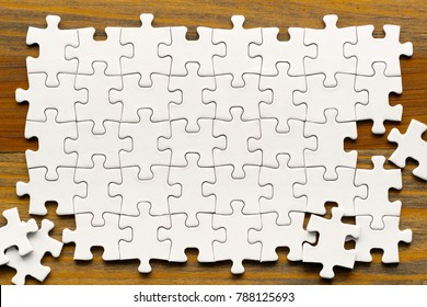 White puzzle pieces on wood background.  Partially completed box shaped pzzle pieces.