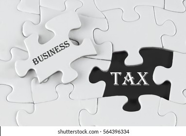 White puzzle with void in the middle when one piece of the puzzle is taken out with text written Business Tax