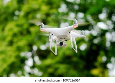White quadcopter with high resolution digital camera for a professional aerial video and photo over green trees background. Operation of drone in air