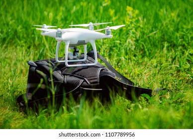 White quadcopter with high resolution digital camera for a professional aerial video and photo on backpack over green grass background.