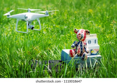 White quadcopter for professional aerial photo and video of July 4th holiday, calendar and teddy bear in USA national flag colors