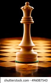 White Queen chess piece on chessboard