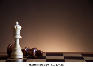 White queen defeats king in chess game, symbol of victory on the chessboard, wooden chess figures on a brown gradient background