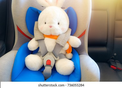 white rabbit on kid car seat and fastened, seat belt or safety belt in the back seat of a car, safety first on the road